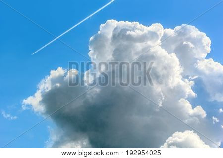 Blue sky with white cumulus cloud and contrail on a summer day close-up