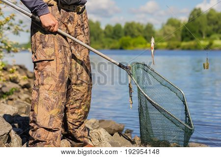 An unrecognizable middle-aged fisherman with an old net with a hole and a small freshly caught fish on the line. Concept of an active lifestyle at any age