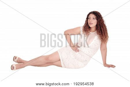 A beautiful woman in a white dress sitting on the floor with her long curly brunette hair isolated for white background.