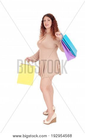 A beautiful woman in a short beige dress holding her shopping bags standing full lengths isolated for white background.