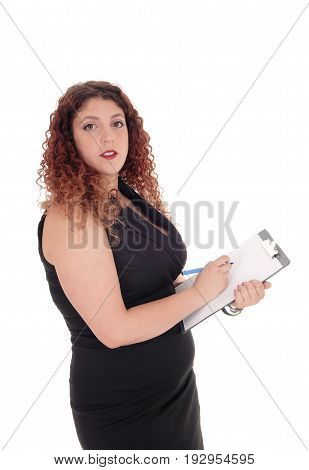 A young business woman stand in in a black dress writing on her clip board looking into the camera isolated for white background.