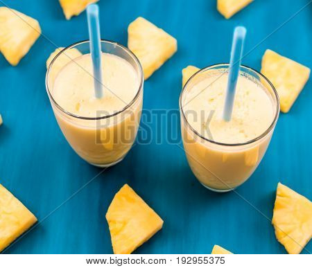pineapple smoothie on a blue background top view