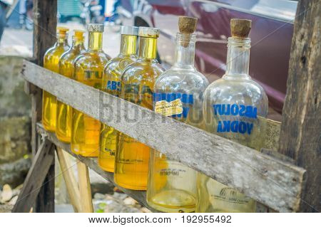 BALI, INDONESIA - MARCH 08, 2017: Illegal gasoline petrol is sold at the side of the road, recycled glass vodka bottles in Bali, Indonesia.