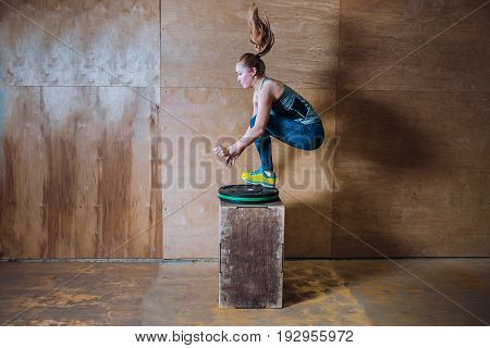 Sporty fit yuong woman jumping over high box during fitness workout, Side view