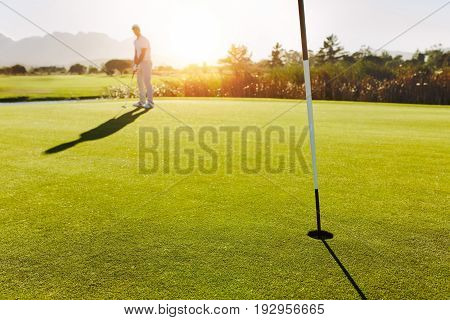 Golf hole and flag in the green field with player in background. Professional male golfer putting the ball.