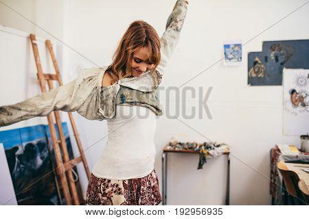 Female painter getting ready in her studio. Caucasian woman artist wearing a shirt before starting work.