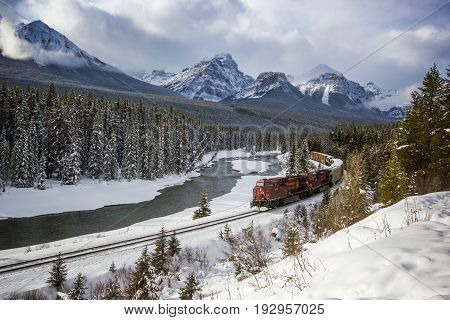 Train passing through river valley under the surveillance of mighty winter and snowy Rocky Mountains, Morants curve, Banff national park, Canada