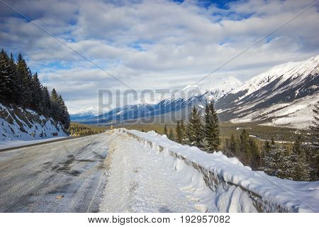 Narrow and slippery winter road with big snowbanks curving down from mountain, Banff national park, Canada