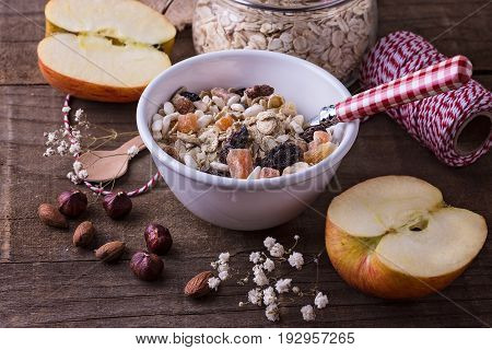 White ceramic bowl of healthy gluten free muesli with dried berries almonds and hazelnuts over rustic wooden background. Clean eating Healthy living Vegan Vegetarian Gluten free food concept