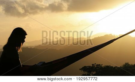 Woman reading a book in front of a black and grey mountain silhouette, San Ramon, Nicaragua, Central America