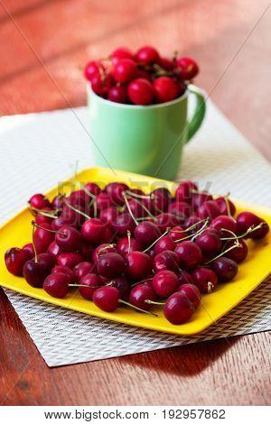 Fresh cherries in bowl on table. Cherries. Sweet Cherries. Fresh Cherries. Ripe cherries on wooden concrete table - board.