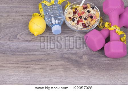 Muesli, Water Bottle, Lemon And Weights On A Wooden Backgraund