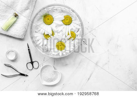 Spa composition on white desk with chamomile, towel and manicure set copyspase top view.