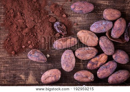 Raw cacao beans and cocoa powder on a rustic wooden background. Top view close up