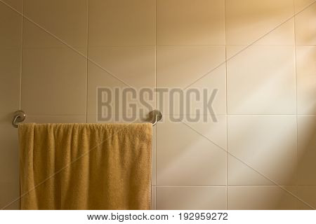 Brown color towel hanging on towel bar in the bathroom with textile background and morning sunlight during shower