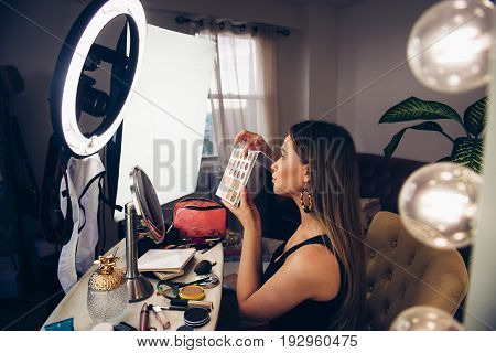 Beauty blogger woman showing cosmetics and telling makeup turtorial and taking video on camera