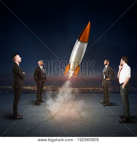 Team of businesspeople looks start a missile in the sky. Concept of company startup and new business. 3D Rendering.