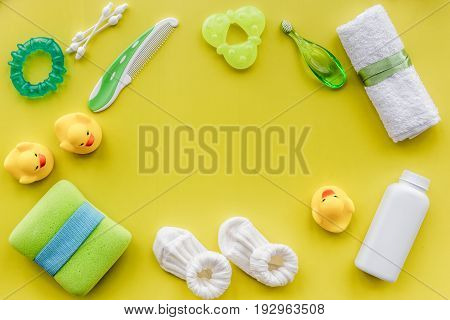 baby accessories for bath with body cosmetic and toy ducks on yellow background top view mock-up