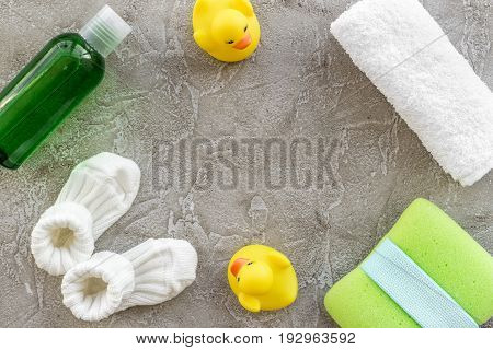 baby accessories for bath with body cosmetic and toy ducks on gray background top view mock-up