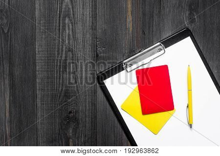 Yellow and red referee cards on wooden background top view.