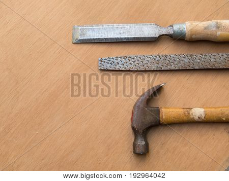 Old carpentry tools, hammer, rasp and chisel, on wooden board