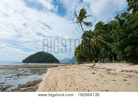 EL NIDO, PALAWAN, PHILIPPINES - MARCH 29, 2017: Girl playing at swing at Las Cabanas Beach in a wide angle view.