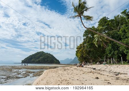 EL NIDO, PALAWAN, PHILIPPINES - MARCH 29, 2017: A swing in the tree sand and rocks at Las Cabanas Beach.