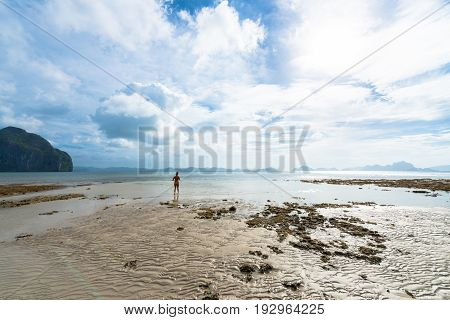 EL NIDO, PALAWAN, PHILIPPINES - MARCH 29, 2017: Wide angle view of a lonely woman getting tan at Las Cabanas Beach.