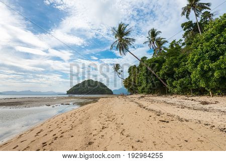 EL NIDO, PALAWAN, PHILIPPINES - MARCH 29, 2017: Wide angle view of the sand rocks and trees at Las Cabanas Beach.