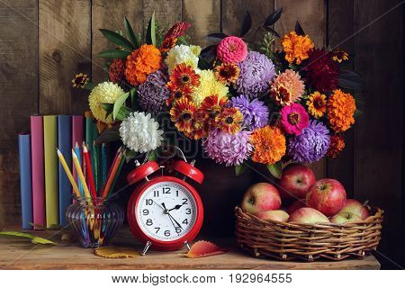 Back to school. Alarm clock bouquet apples in basket and books on the table. Rural still life.