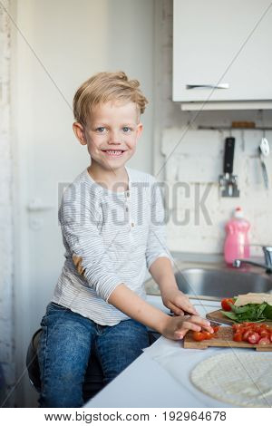 Handsome boy is cooking in the kitchen at home. Healthy food