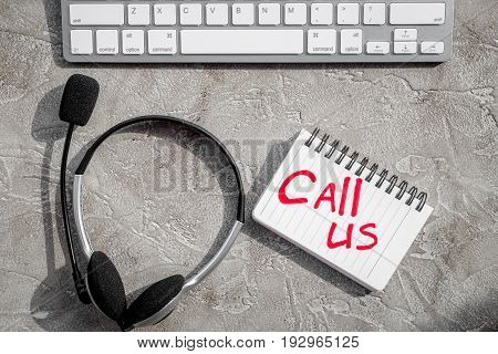 operator headset, notebook and keyboard for contact us feed back on call center workdesk stone background top view