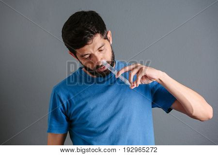Nasal wash. Man flushing his nose with syringe and saline isolated on gray background poster