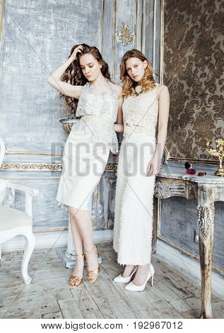 two pretty twin sisters in luxury house interior together, rich young people concept