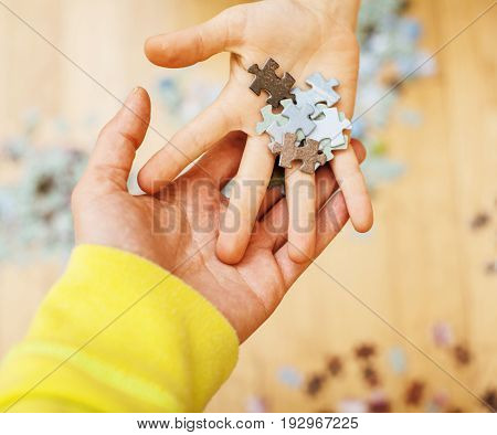 little kid playing with puzzles on wooden floor together with parent, lifestyle people concept, loving hands to each other, warm wooden home interior close up