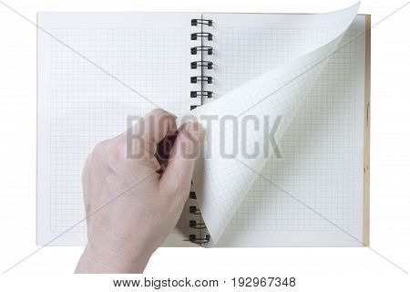 Hand turns the notebook page on white background