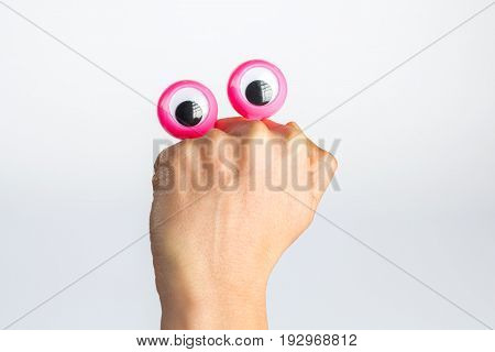 Funny Character Creature Hiding Behind Female Hand With Googly Eyes. Isolated On White With Copy Spa