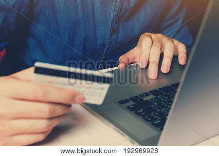 Close up smart young man typing trackpad on laptop with shopping online or internet banking concept.