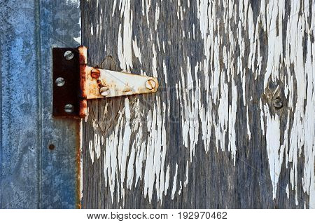 An abstract image of an old rusted door hinge with white peeling paint.