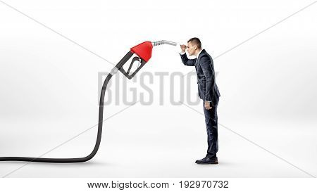 A businessman on white background staring closely at a large red gas nozzle attached to a black hose. Gas station business. Delivery expenses. Fuel market.