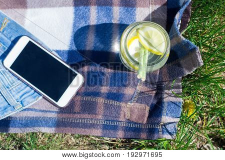 Fresh lemon lemonade in jar on plaid on grass. Citrus summer drink. Top view copy space