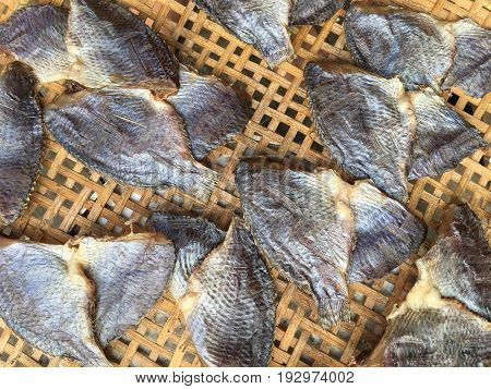dry salty nile tilapia fish on bamboo floor