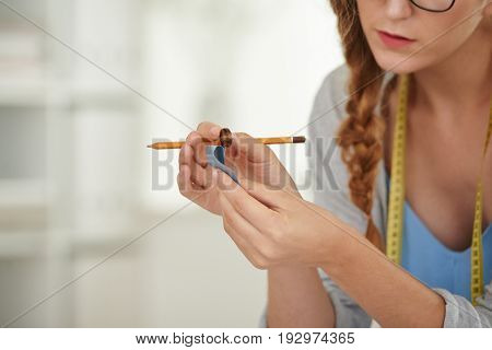Tailor checking if button suits to the cloth in her hands