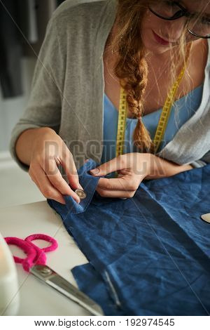 Close-up image of woman sewing buttons on clothing item
