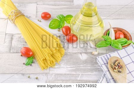 Italian spaghetti pasta and fresh ingredients on a rustic wooden background