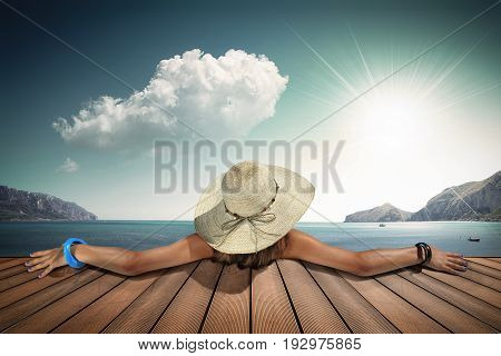 girl with straw hat shoot by back while sunbathing on the pier