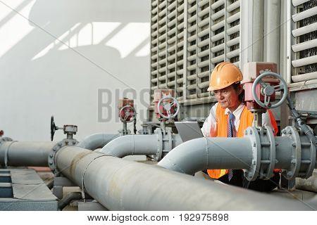 Vietnamese worker reading instruction before repairing plant equipment