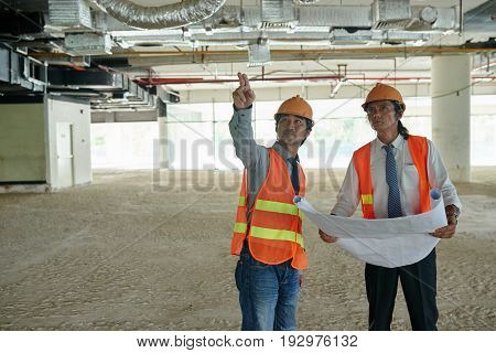 Engineer showing his coworker where the problem with communications is