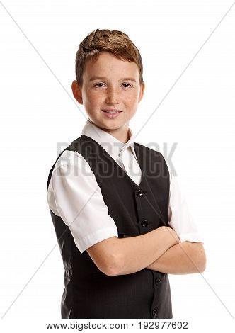 Portrait of smiling boy in school uniform with crossed hands