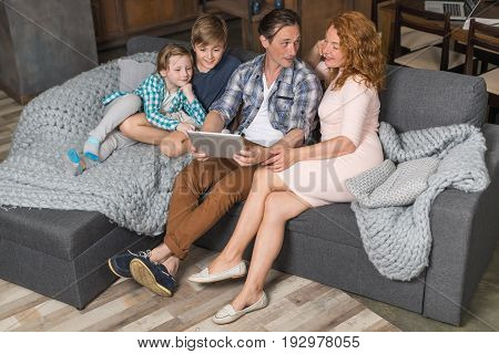 Happy Smiling Family Use Tablet Computer Sitting On Couch In Living Room Top Angle View, Parents Spending Time With Son And Daughter Surfing Internet